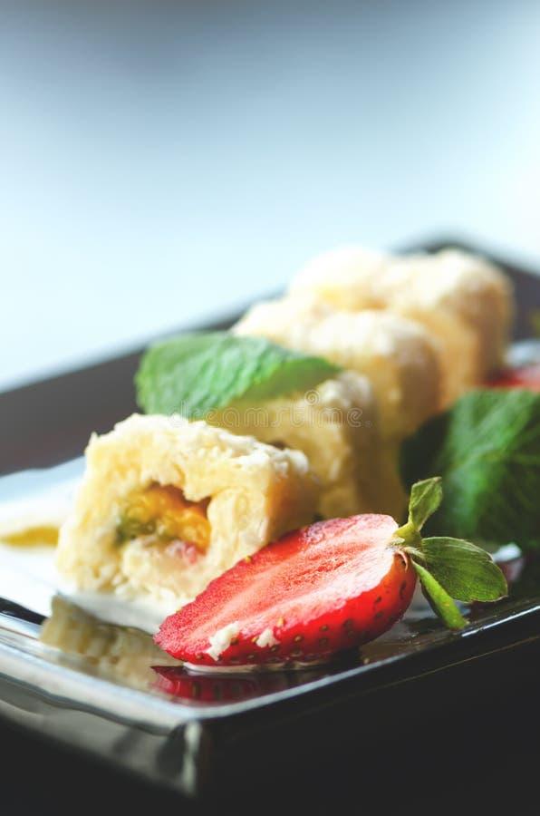 Rotolo dolce bianco con il kiwi, pesche, fragole, menta Serverd con le salse della pesca e di cioccolato della mandorla sulla ban fotografia stock
