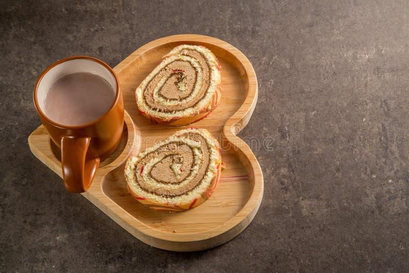 Rotolo dolce con crema con cioccolato al latte caldo su un vassoio in forma di cuore di legno immagini stock