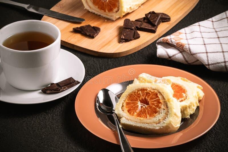 Rotolo dolce con il materiale da otturazione montato del mandarino e della crema e una tazza di tè fotografie stock libere da diritti