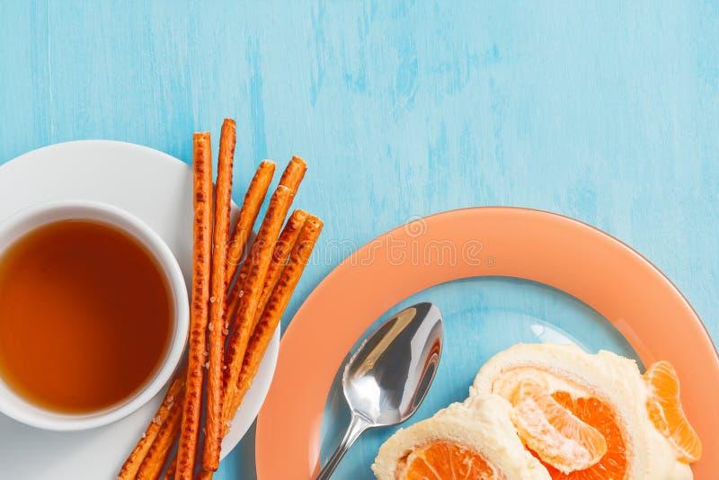 Rotolo dolce con il materiale da otturazione montato del mandarino e della crema e una tazza di tè fotografia stock libera da diritti
