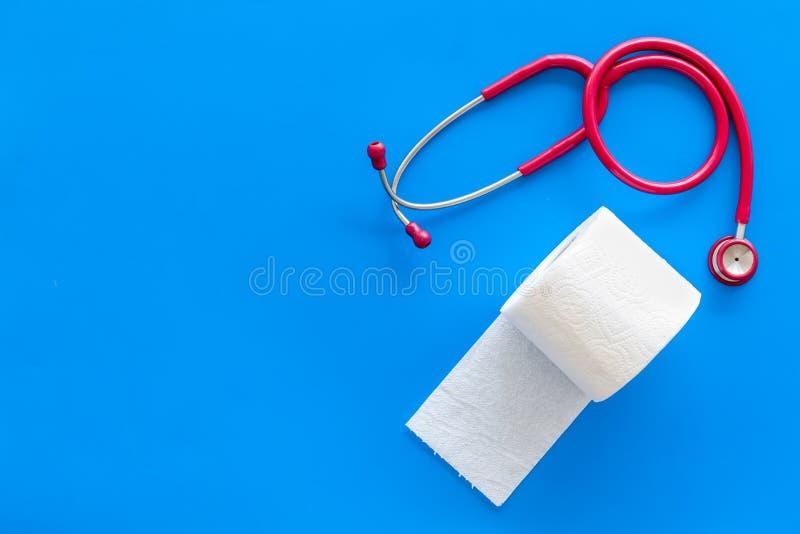Rotolo e stetoscopio della carta igienica per il concetto di malattie di proctologia su derisione blu di vista superiore del fond immagini stock