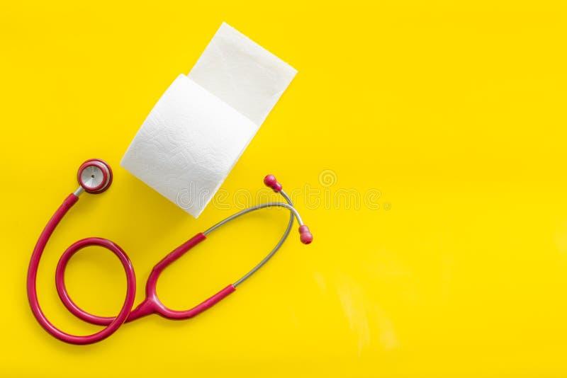 Rotolo e stetoscopio della carta igienica per il concetto di malattie di proctologia su derisione gialla di vista superiore del f fotografia stock libera da diritti