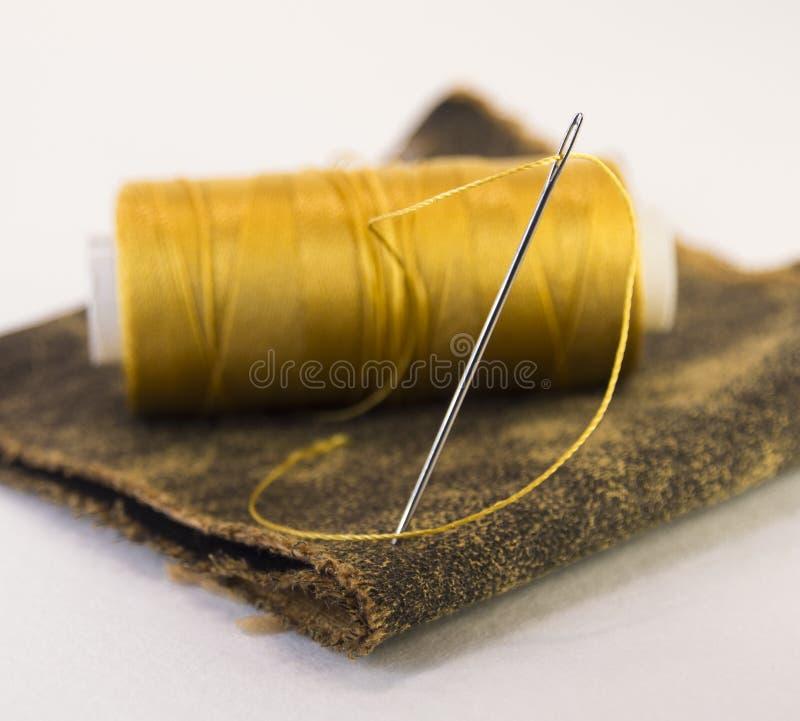 Rotolo variopinto del filo su un pezzo di cuoio con un ago fotografia stock libera da diritti