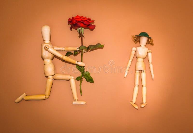 Rotrose und hölzerner Mann, Frau auf braunem Hintergrund stockbild