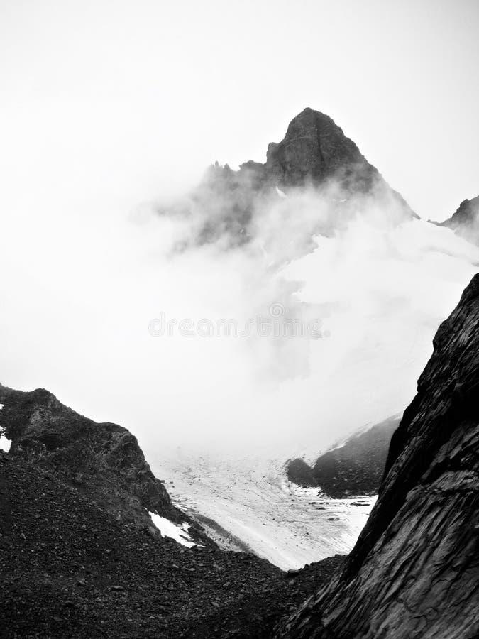 Rots en ijs en mistige bergen met gletsjerpiek stock afbeeldingen
