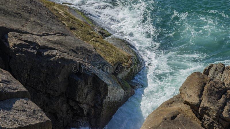 Rots in het overzees De golven die op een steenachtig strand breken stock afbeeldingen