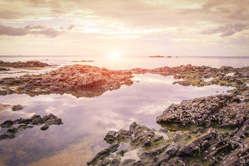 Rots op het strand en de zonsondergang royalty-vrije stock afbeelding
