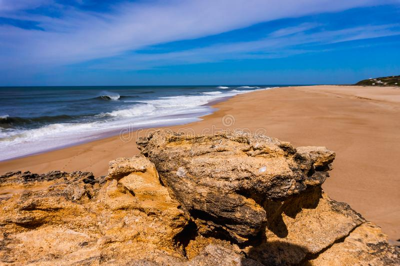 rots op strand in Nazare op Atlantische kust met oceaangolf royalty-vrije stock afbeelding