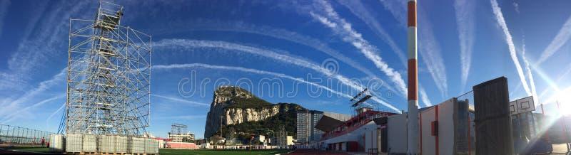 Rots van het panorama van Gibraltar met Victoria Stadium en hemel met vliegtuigstroken stock foto