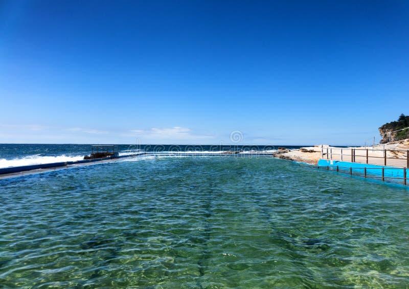 Rots zwembad die in de Vreedzame Oceaan stromen stock afbeeldingen