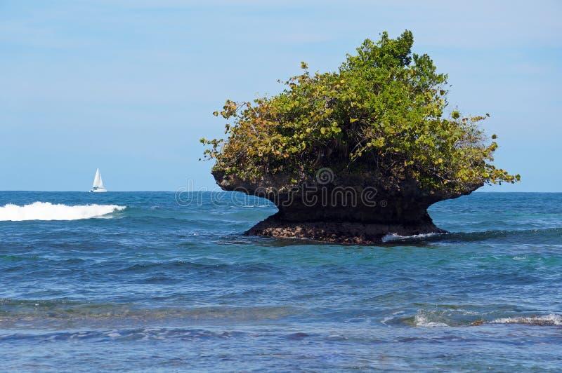 Rotsachtig die eilandje door de golven wordt geërodeerd royalty-vrije stock foto