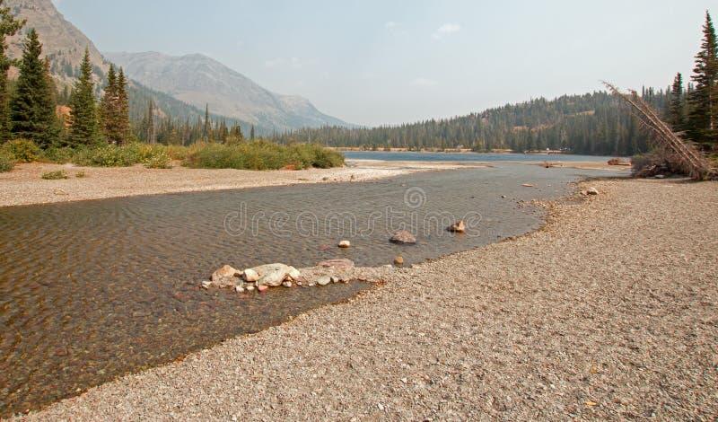 Rotsachtige en grintachtige oever van Hoger Twee Geneesmiddelen Meer in Gletsjer Nationaal Park tijdens de de dalings bosbranden  royalty-vrije stock foto's
