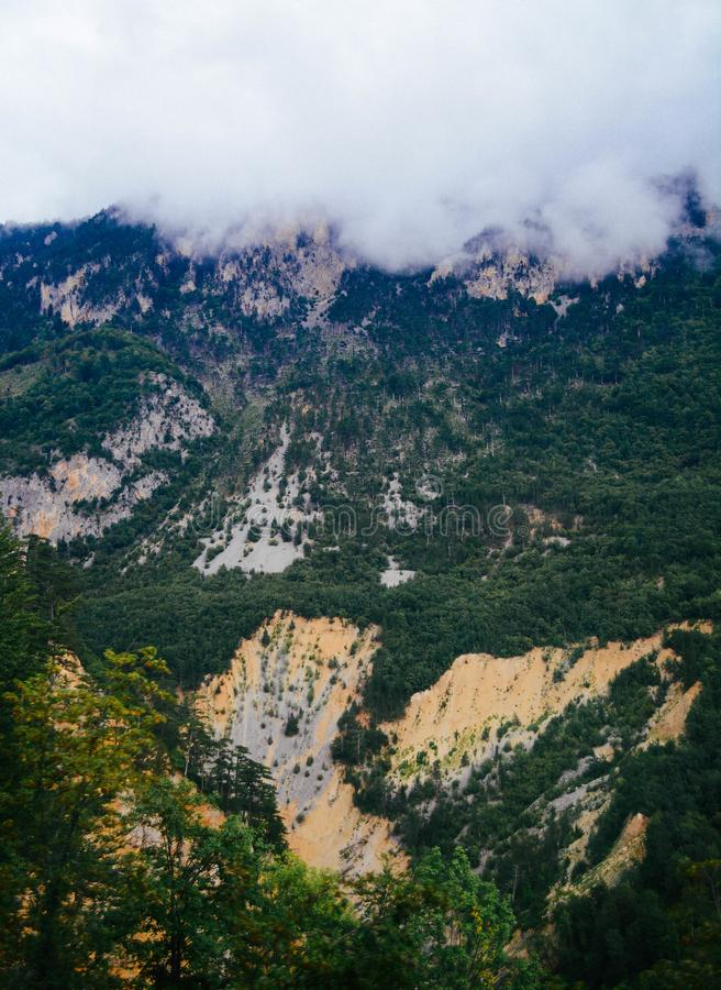 Rotsachtige hellingen van de bergen en de mist die hen absorbeert stock foto's