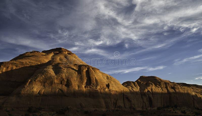 Rotsachtige heuvels die door de zonsondergang in Monumentenvallei worden geïnformeerd stock foto's