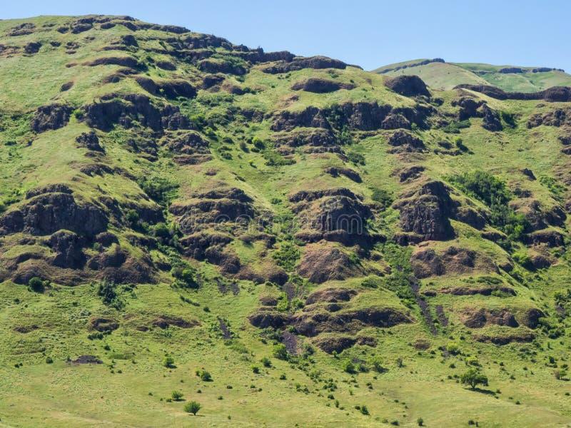 Rotsachtige klippen en groen gras royalty-vrije stock afbeeldingen