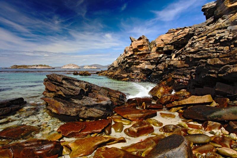 Rotsachtige kust met donkerblauwe hemel met witte wolken Overzees met donkerblauwe hemel Stenen in het overzees Oceaankust met ro royalty-vrije stock fotografie