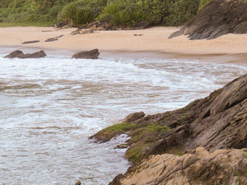 Rotsachtige kust met golven het verpletteren en strand op achtergrond stock fotografie
