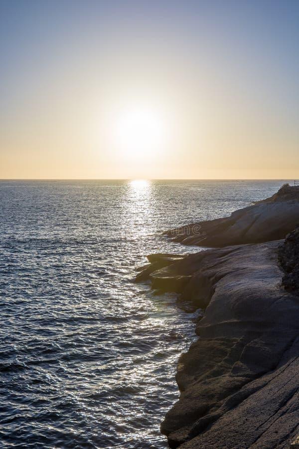 Rotsachtige kust met kalme overzees en een romantische zonsondergang stock foto