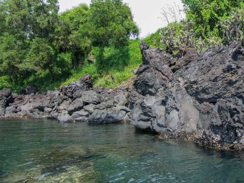 Rotsachtige kust met tropische vegetatie Klippen die boven de oppervlakte uitpuilen Kalme overzees en zonovergoten kustlijn stock afbeeldingen