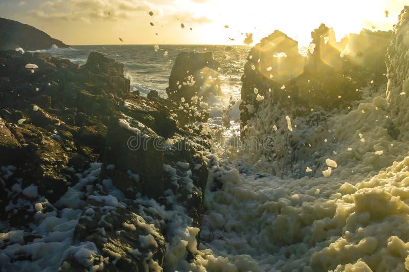 Rotsachtige kust tijdens een zonsondergang stock foto's