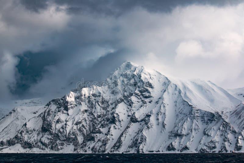 Rotsachtige kust van één van de Kuril Eilanden in de winter tijdens een sneeuwonweer royalty-vrije stock afbeelding