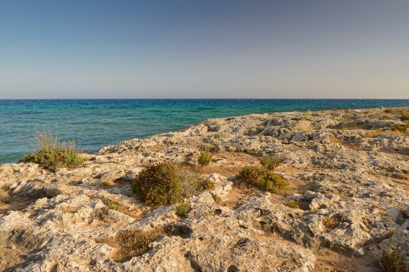 Rotsachtige kust van de Middellandse Zee bij zonsondergang stock fotografie