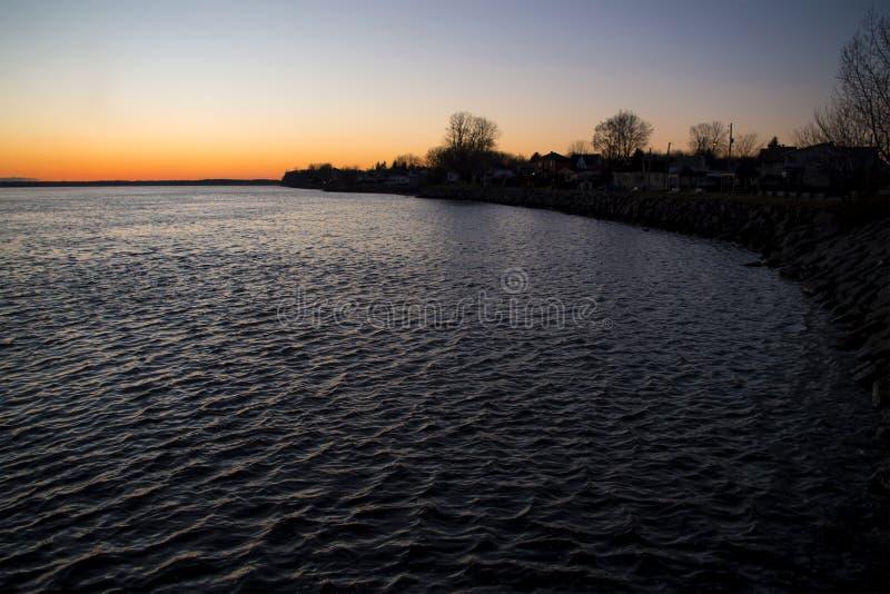 Rotsachtige kust van een rivier in de zonsondergang royalty-vrije stock foto