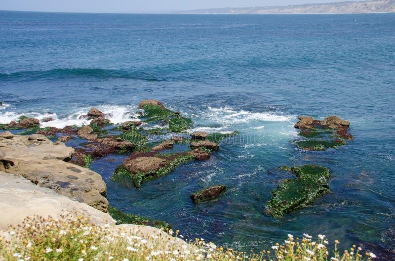 Rotsachtige kustlijn die van La Jolla Californië, uit in de vreedzame oceaan kijken royalty-vrije stock afbeelding