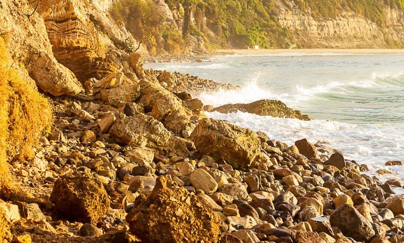 Rotsachtige oever met klip, golf het breken door baai royalty-vrije stock fotografie