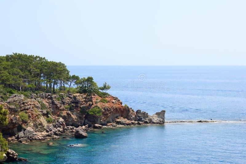Rotsachtige overzeese die kust door pijnbomen in Kemer, Antalya, Turkije wordt behandeld stock foto's