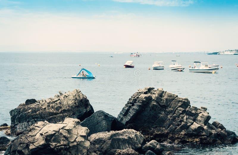 Rotsachtige overzeese kust van Acitrezza naast Cyclops-eilanden met de achtergrond van zeilboten, Catanië, Sicilië, Italië stock foto