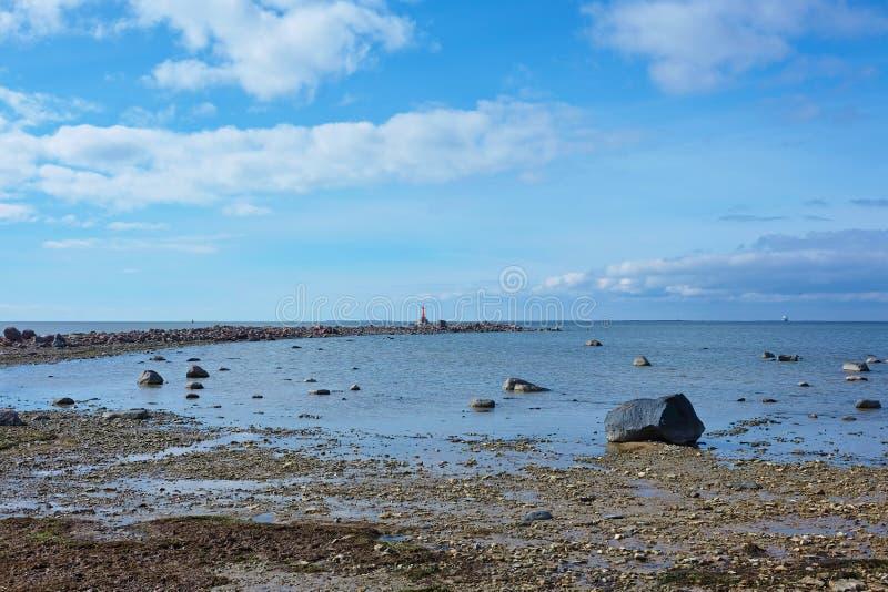 Rotsachtige strand en vlecht met een kleine vuurtoren royalty-vrije stock afbeelding