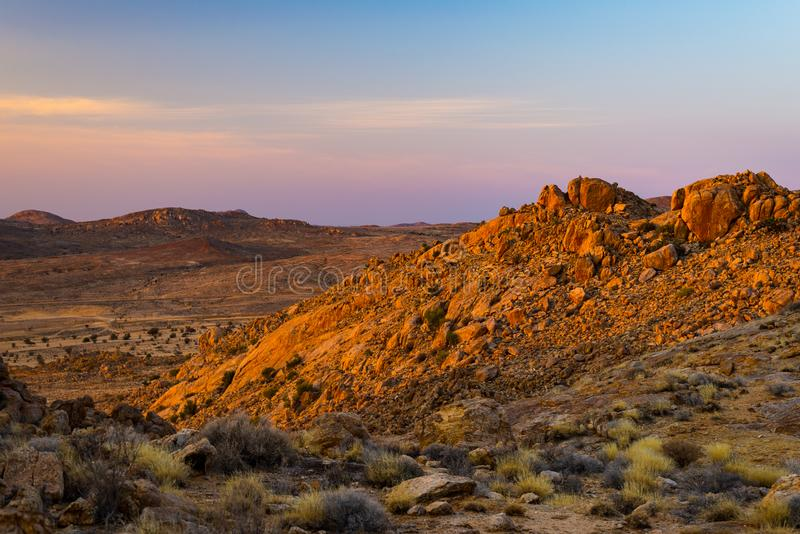 Rotsachtige woestijn bij schemer, kleurrijke zonsondergang over de Namib-woestijn, Namibië, Afrika, gloeiende rotsen en canion stock foto's
