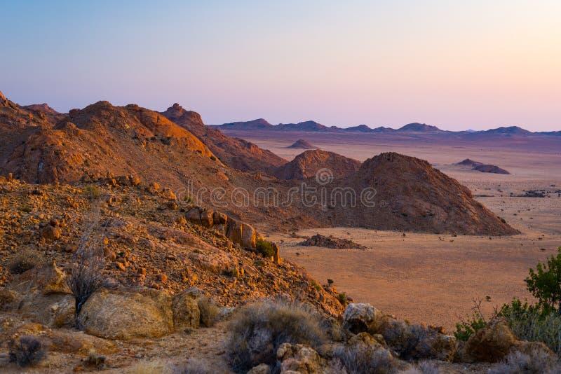 Rotsachtige woestijn bij schemer, kleurrijke zonsondergang over de Namib-woestijn, Namibië, Afrika, gloeiende rotsen en canion stock fotografie