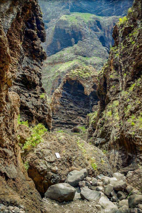 Rotsen in de Masca-kloof, Tenerife, die de hard gemaakte vulkanische lagen van de lavastroom en boogvorming tonen De ravijn of ba royalty-vrije stock afbeelding
