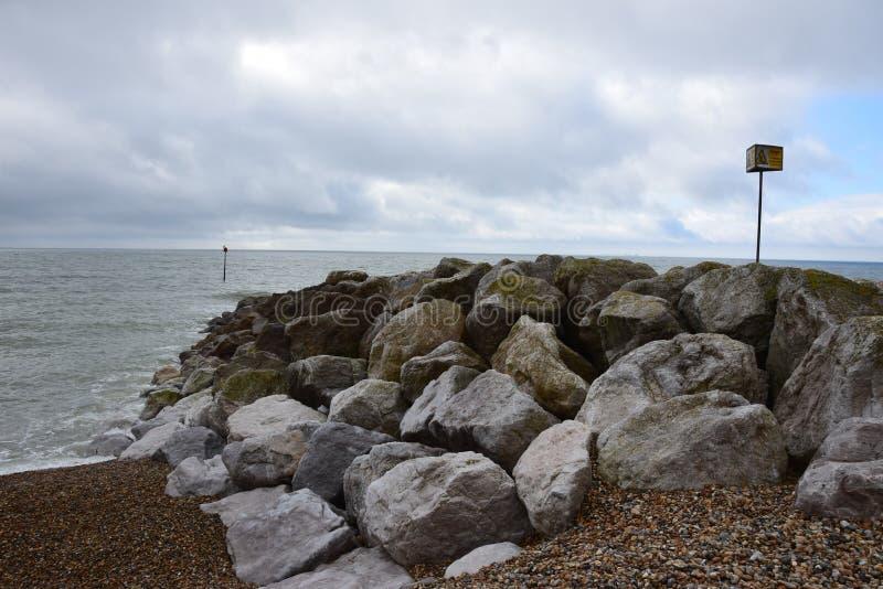Rotsen die als wateronderbreking worden gebruikt op het strand stock afbeeldingen