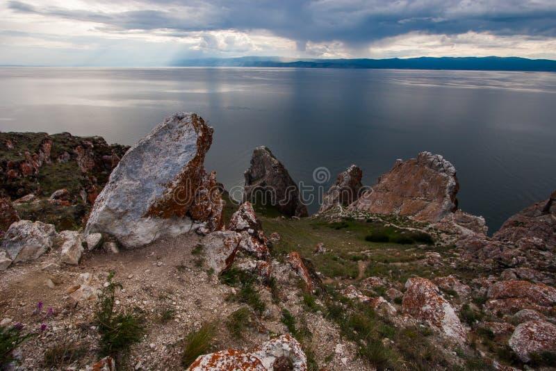 Rotsen Drie Broers op het Eiland Olkhon op het meer van Baikal Hemel met wolken Op de stenen is rood mos en rond groen gras stock fotografie