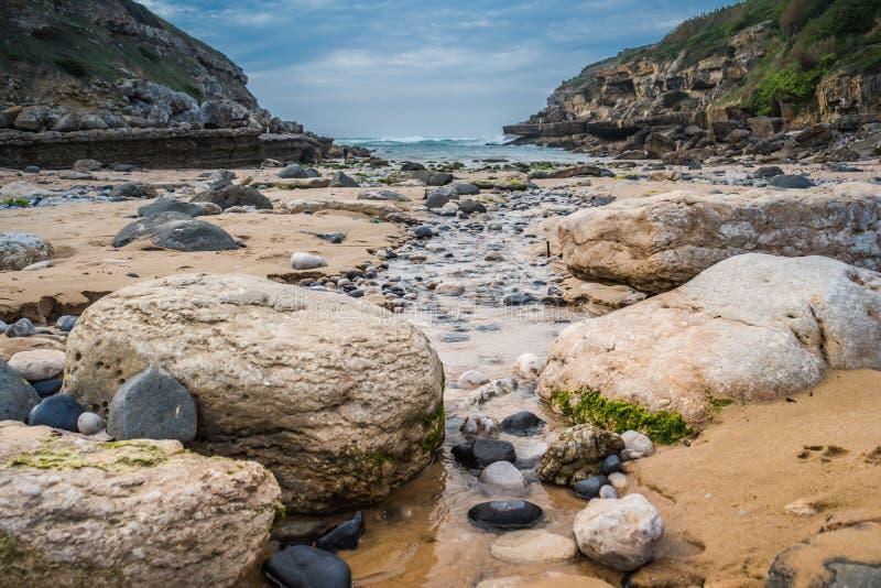 Rotsen en kleine stroom van water die tegen het overzees, in Praia DA Samarra te gaan, door bergen, Sintra - Lissabon, Portugal w royalty-vrije stock afbeeldingen