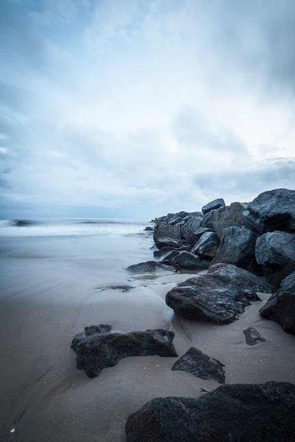 Rotsen op de oceaan van de strandzonsondergang royalty-vrije stock afbeeldingen