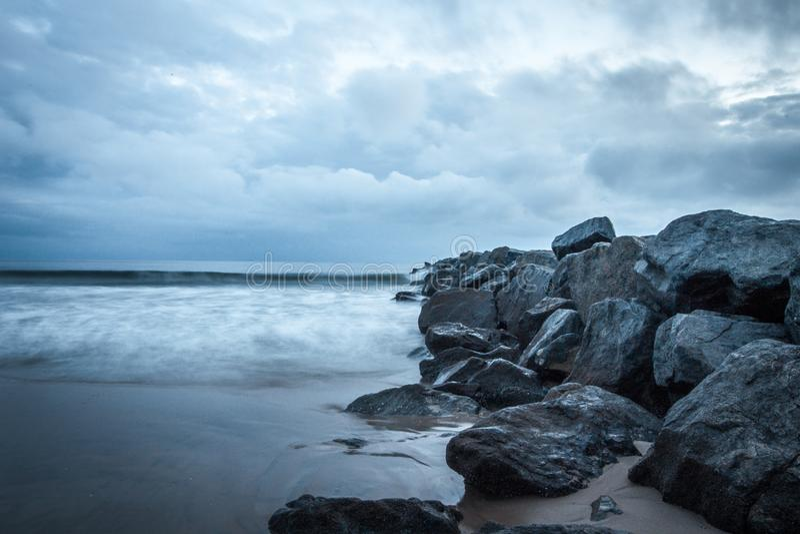 Rotsen op de oceaan van de strandzonsondergang stock foto's