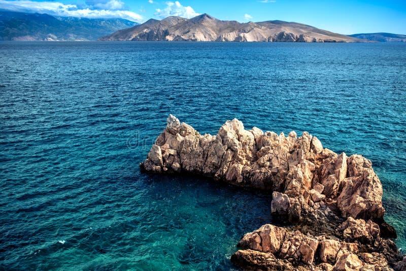 Rotsen op klippen en golven in de oceaan, van een strand wordt gezien dat Kalm water, duidelijke hemel en golven op een zonnige d royalty-vrije stock afbeelding