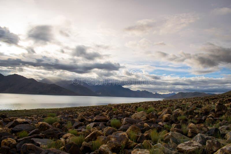 rotsen op van de de kustberg van het pangongmeer bewolkte hemel als achtergrond royalty-vrije stock afbeelding