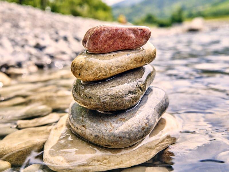Rotsen, rivierkiezelstenen in een stroom worden gestapeld die stock afbeelding