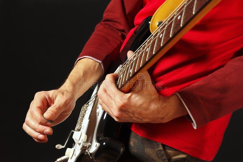 Rotsgitarist gezette vingers voor snaren op elektrische gitaar op zwarte achtergrond stock foto's