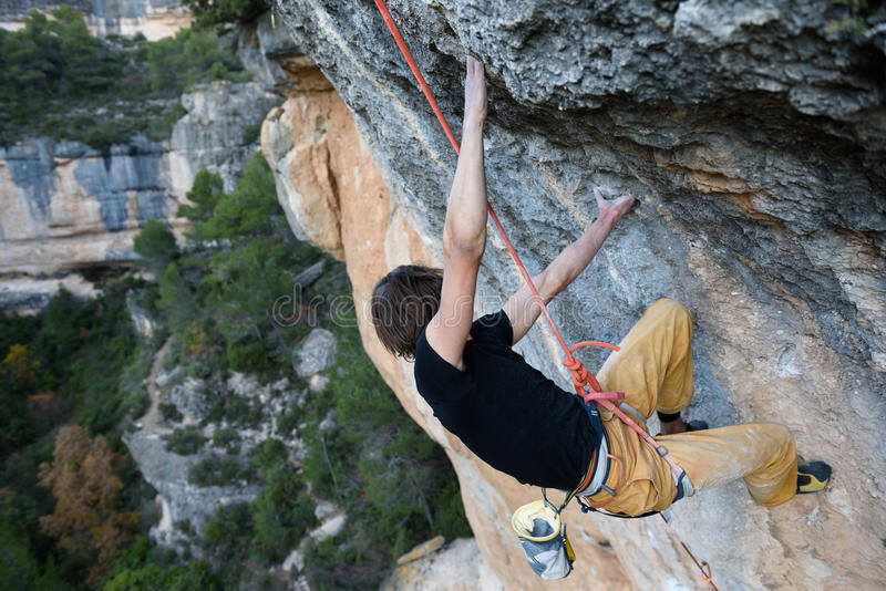 Rotsklimmer die een uitdagingsklip stijgen Extreme sportclimbi royalty-vrije stock afbeelding