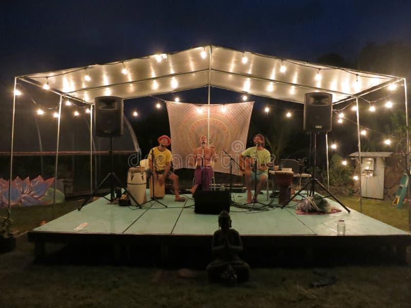 Rotsmusici Paul Izak en vrienden die muziek spelen in Yogarden onder behandeld licht stadium royalty-vrije stock foto