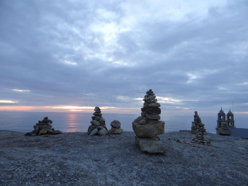 Rotstoren op Spaanse kust dichtbij kerk en zonsondergang royalty-vrije stock foto's