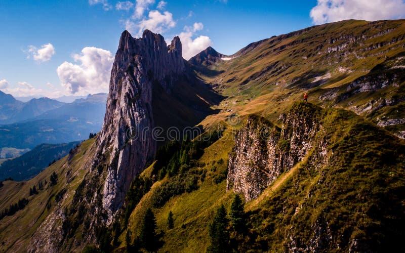 Rotsvorming in de Zwitserse bergen alpstein, kerel die zich bovenop een berg bevinden stock afbeelding