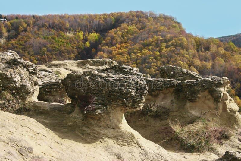Rotsvormingen, bergen in Caucas, Rusland met de herfst bosmening Georgeouslandschap met klip en bos Multicolored yel stock afbeelding