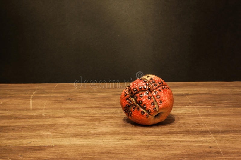 Rotten genetic modified apple. Old style view of the old steam-punk style apple on the wooden oak table and dark background royalty free stock image